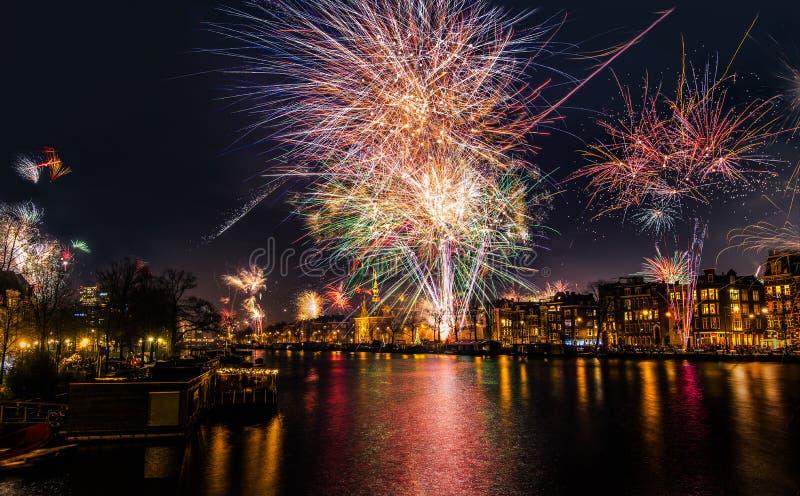Silvesterabendfeuerwerke über dem Amstel-Fluss in Amsterdam, Nordholland, die Niederlande lizenzfreies stockfoto