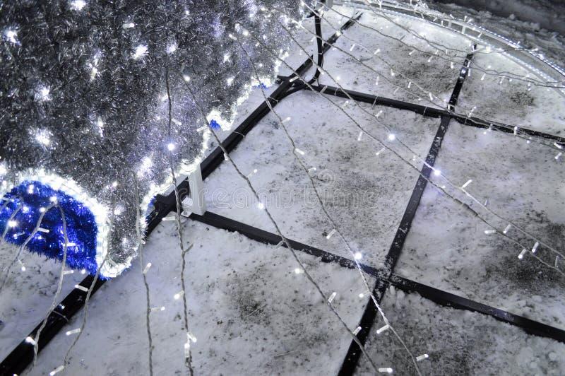Silvrig bakgrund från julpynt, lyktor, ljus, girlander, regn och svart järnkonstruktion royaltyfria foton