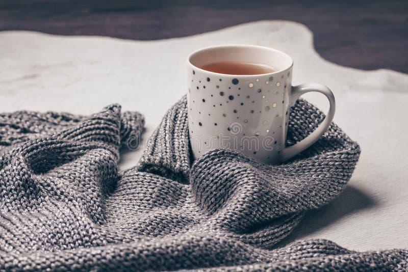 Silvrigt grått stuckit tyg längs en kopp te på mjölkaktig vit pälsbakgrund royaltyfri bild