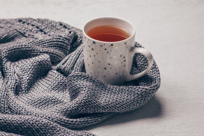 Silvrigt grått stuckit tyg längs en kopp te på mjölkaktig vit pälsbakgrund Få över influensabegrepp royaltyfri bild
