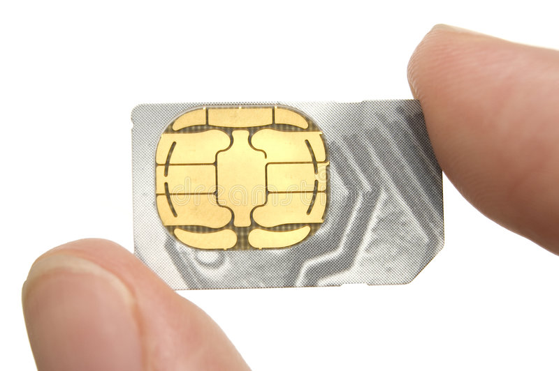 Sim-Card. Man holding a sim-card between his thumb and index finger - closeup on sim-card, fingers are out of depth of field stock image