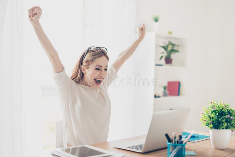 Sim! Estação de trabalho entusiasmado feliz da mulher em casa que triunfa com rai foto de stock