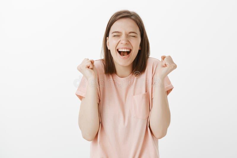 Sim eu ganhei Retrato de triunfar a menina feliz e despreocupada no t-shirt cor-de-rosa, gritando com sorriso largo e os olhos fe imagem de stock