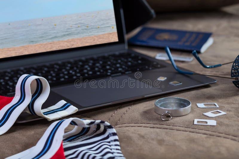 SIM-kort, kompass, solglas?gon och baddr?kt p? en ?ppen modern b?rbar datorbakgrund Semesterplanl?ggning royaltyfri fotografi