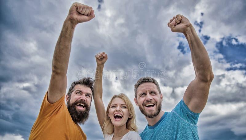Sim n?s podemos A mulher e os homens olham o fundo bem sucedido seguro do c?u Suporte do Threesome feliz seguramente com punhos a fotos de stock royalty free