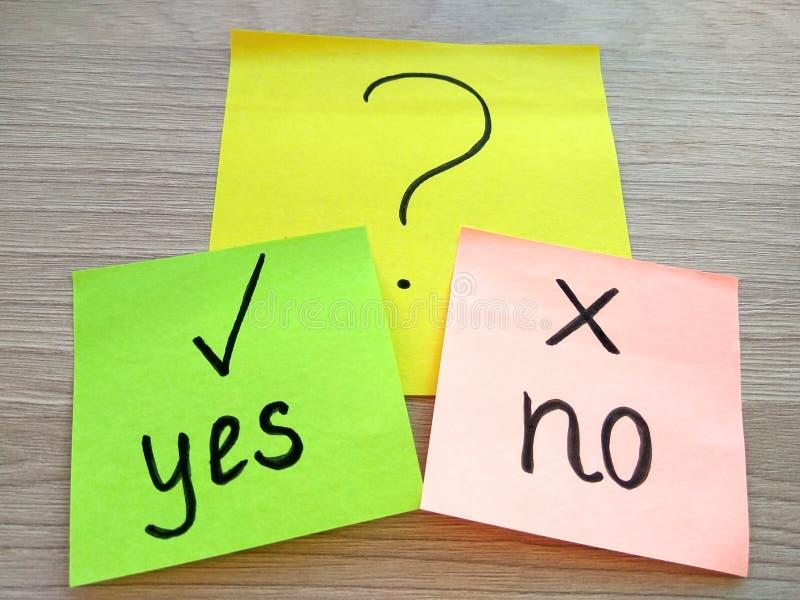 Sim ou nenhuma mensagem da pergunta em notas pegajosas no fundo de madeira da tabela Conceito da resolução de problemas e da es fotografia de stock