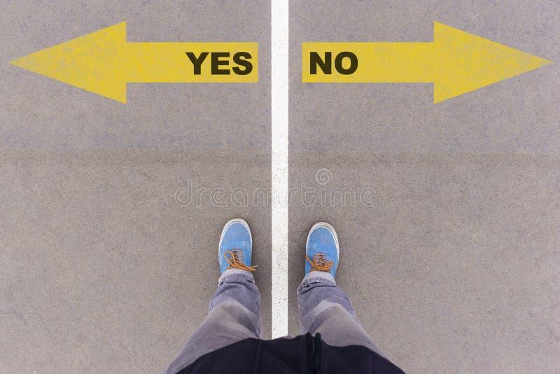 Sim ou nenhumas setas do texto na terra, nos pés e nas sapatas do asfalto no assoalho foto de stock