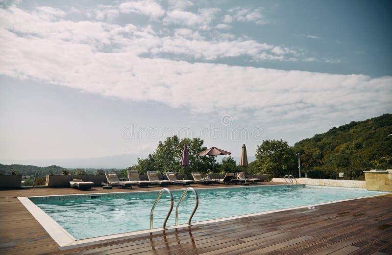Simbassäng med sunbeds och solparaply och berg i bakgrunden fotografering för bildbyråer