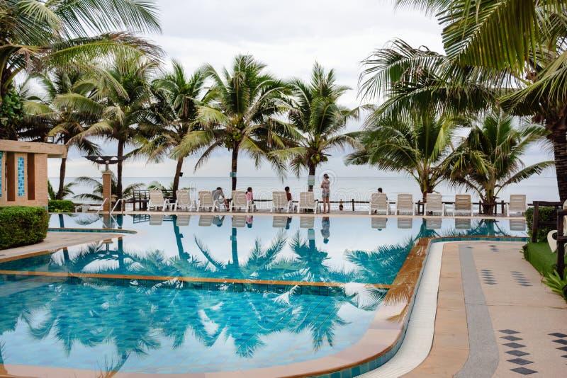 Simbassäng på den tropiska semesterorten nära havet i Thailand Folket kopplar av på de vita stolarna bredvid simbassängen bland fotografering för bildbyråer