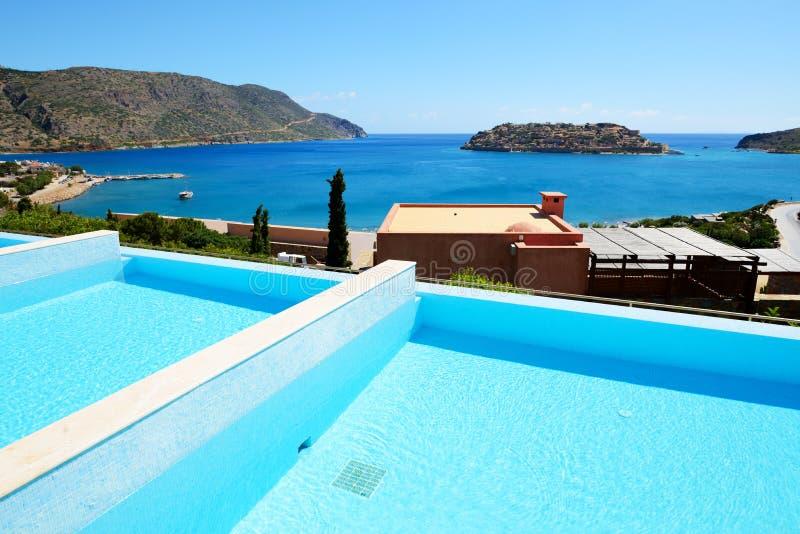 Simbassäng på det lyxiga hotellet med en sikt på den Spinalonga ön fotografering för bildbyråer
