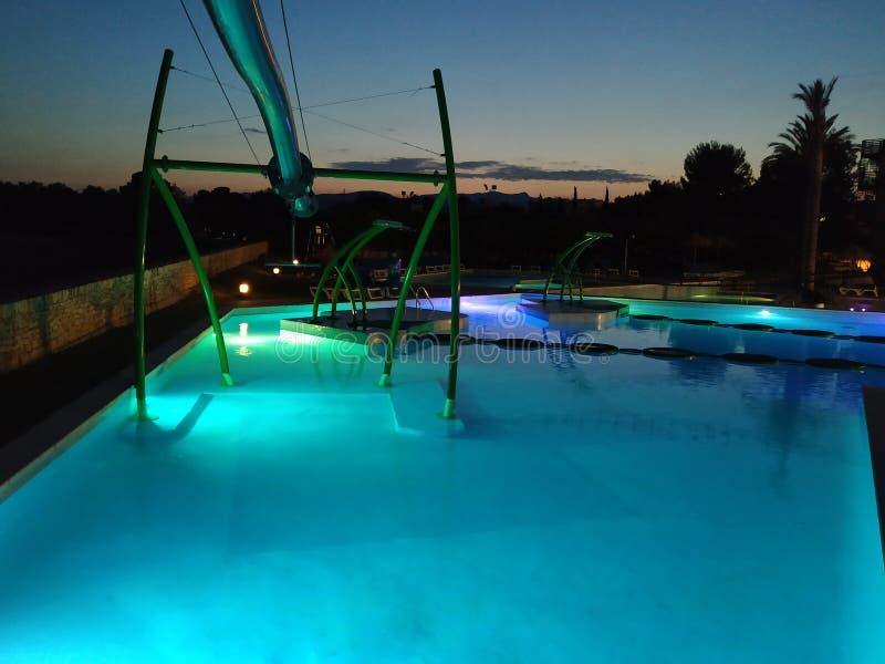 Simbassänger exponerade på natten i ett turist- komplex på den medelhavs- kusten royaltyfri foto