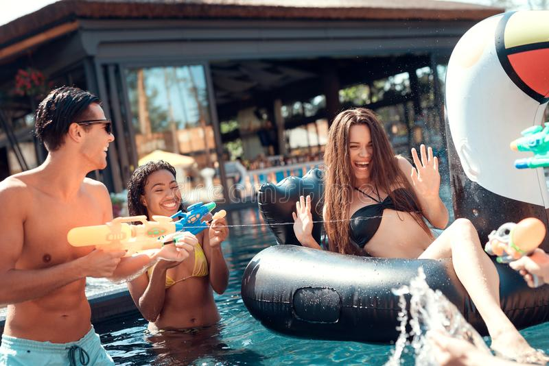 Simbassängparti Grupp människor har gyckel i simbassäng på sommartid royaltyfri fotografi