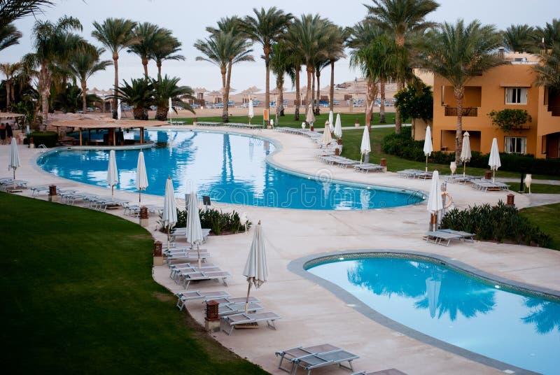 Simbassängsida i semesterort Två simbassänger och gömma i handflatan Töm pölsidan med stängda paraplyer Hotellbyggnader runt om b arkivbild