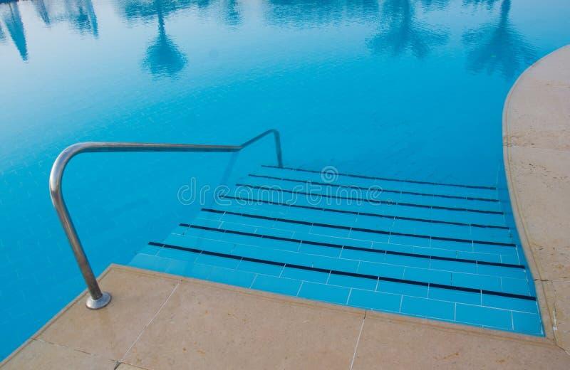 Simbassängtrappan tonar itu av blåttfärg med trädreflexionen på vattnet, bästa sikt royaltyfria foton