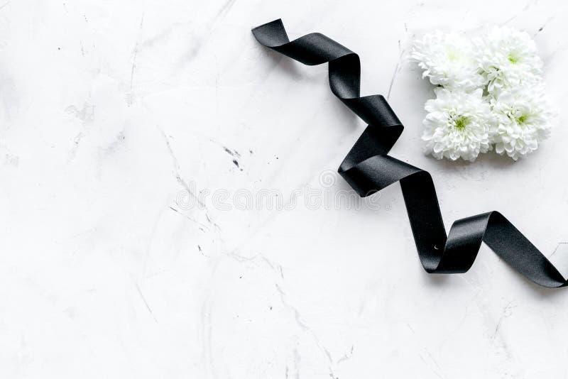 Simboli funerei Fiore bianco vicino al nastro nero sullo spazio bianco della copia di vista superiore del fondo della pietra fotografia stock libera da diritti