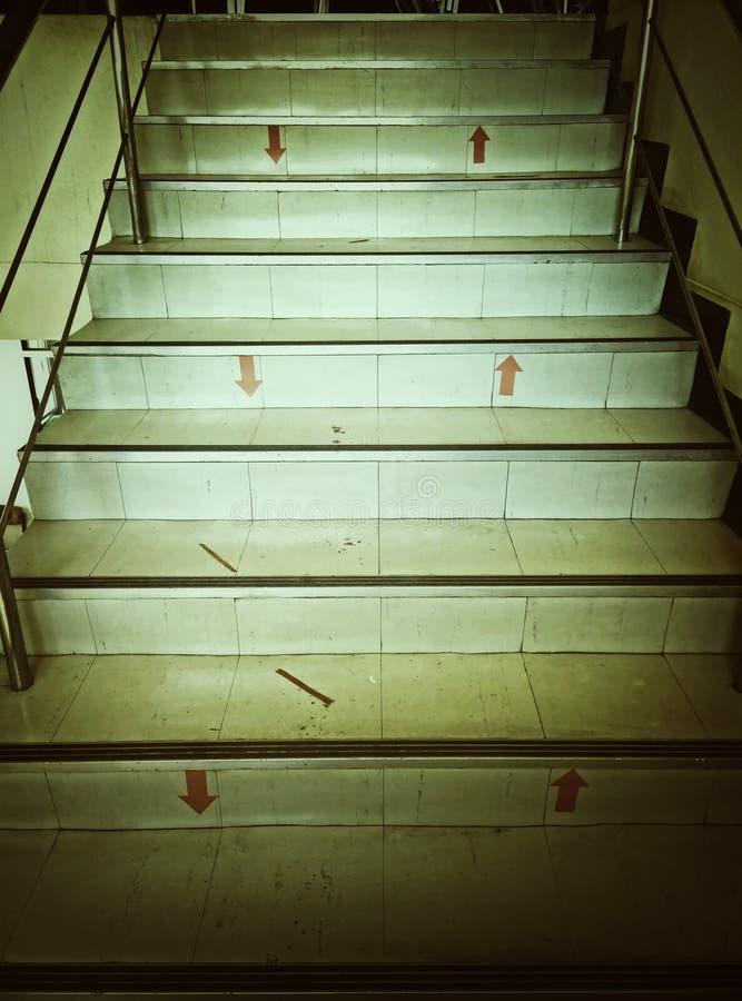 Simbolice las flechas en las escaleras del edificio imagenes de archivo