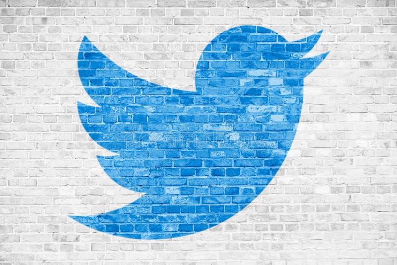 Simbolo blu di logo del segno dell'uccello di media sociali di Twitter nella progettazione minimalista dipinta sopra il fondo bia fotografie stock