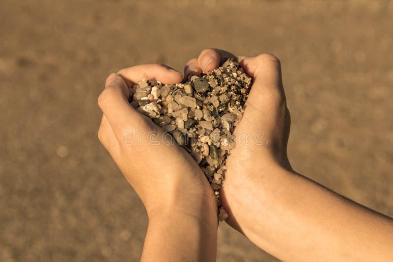 Simbolo del cuore con le mani e le pietre fotografia stock
