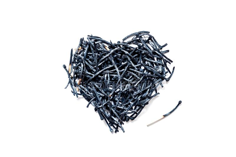 Simbolo del cuore fatto del primo piano bruciato delle partite, isolato su un fondo bianco fotografia stock