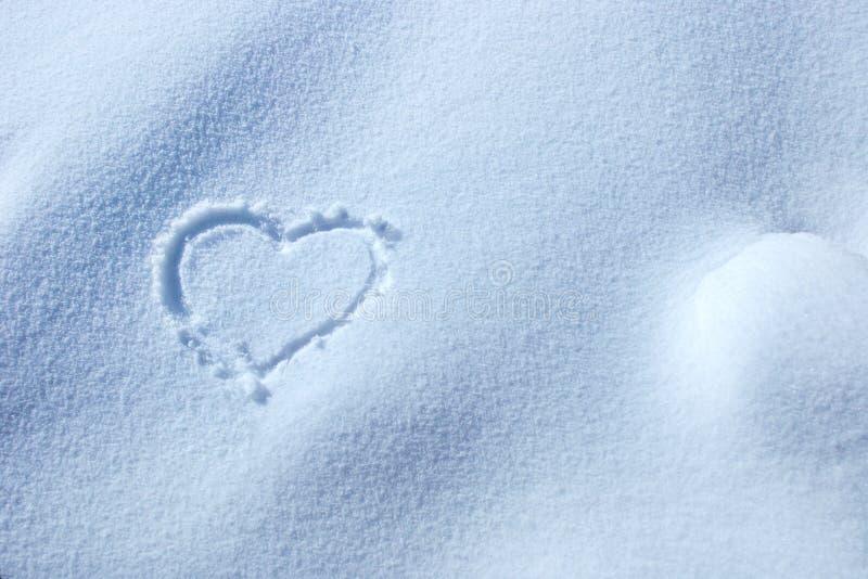 Simbolo del cuore scritto nella neve fotografia stock libera da diritti