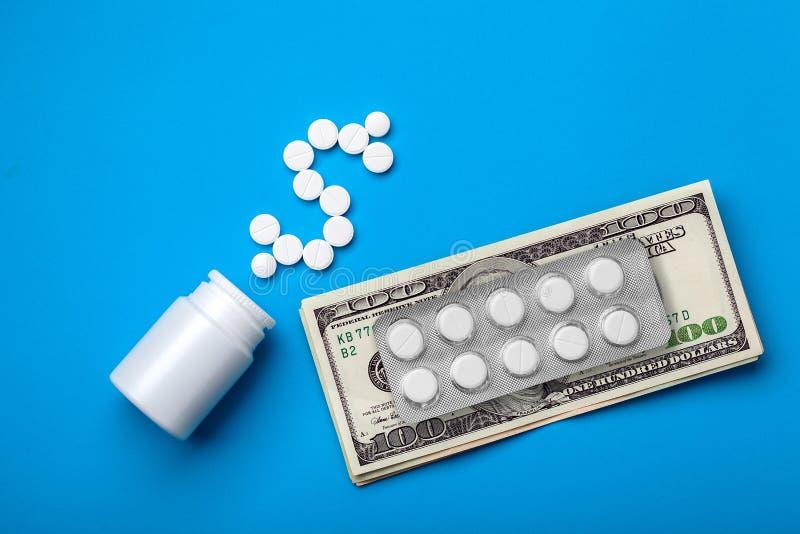 Simbolo del dollaro dalle pillole vicino ad una bottiglia di medicina fotografia stock