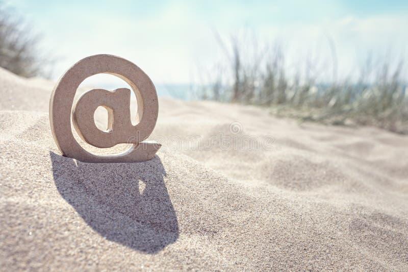 Simbolo del email @ alla spiaggia immagini stock