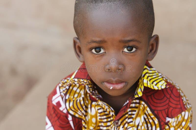 Simbolo dell'Africa di fame - piccolo ragazzo africano con riso sulla bocca fotografia stock libera da diritti