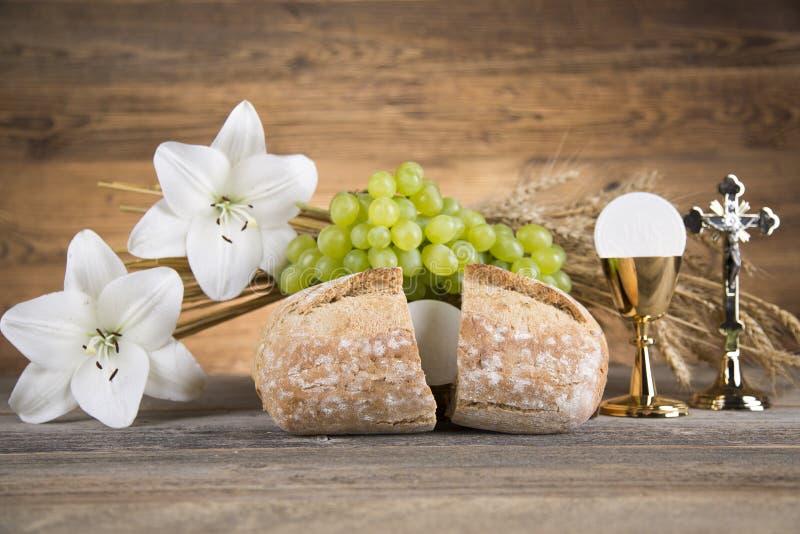 Simbolo dell'eucaristia di pane e vino, calice e ostia, primo comm immagini stock