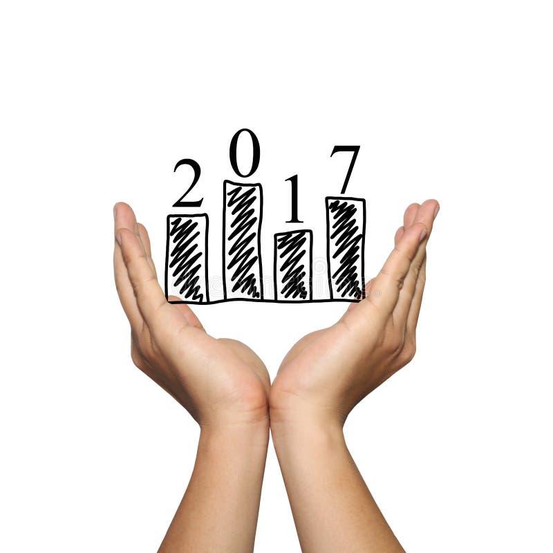 Simbolo dell'istogramma di affari e del numero 2017 sulla mano dell'uomo in concentrato immagine stock