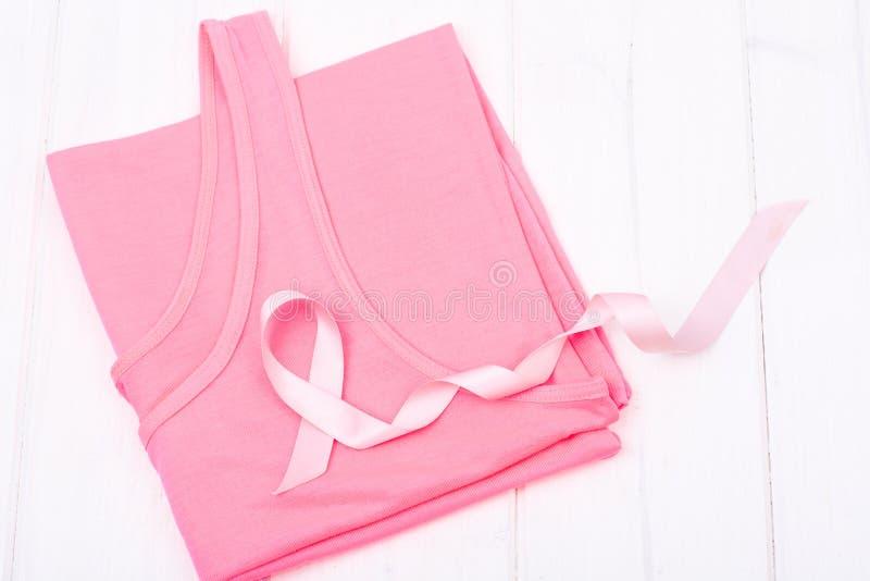 Simbolo della medicina e di sanità - nastro rosa di consapevolezza del cancro al seno sulla camicia femminile fotografia stock libera da diritti