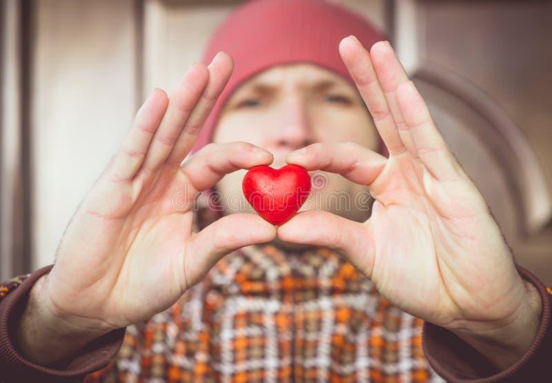 Simbolo di amore di forma del cuore in mano dell'uomo con il fronte il giorno dei biglietti di S. Valentino del fondo immagini stock libere da diritti