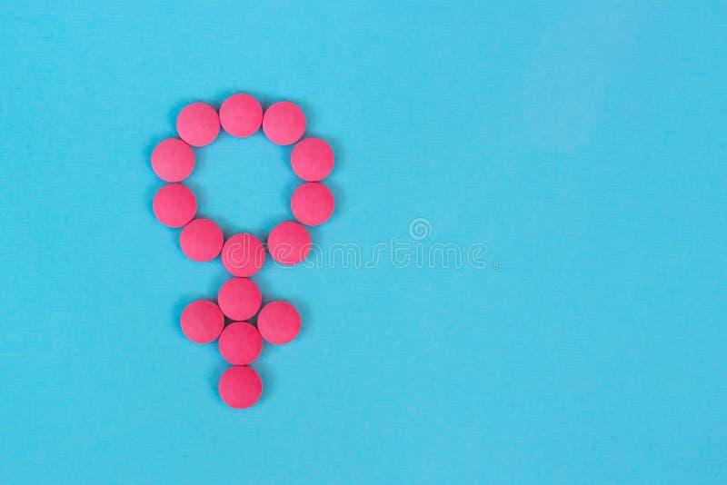 Simbolo di genere della donna dalle pillole di rossi carmini sulla vista superiore del fondo blu con lo spazio della copia, conce immagine stock libera da diritti