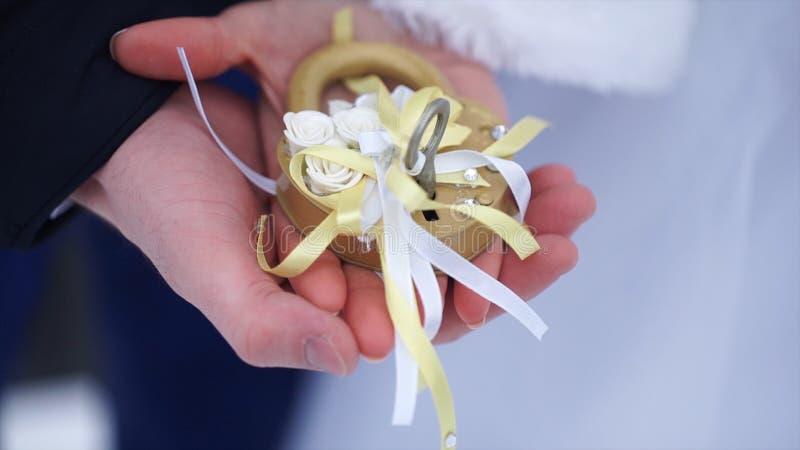 Simbolo di nozze, serratura in mani della sposa e sposo Le persone appena sposate riparano il fissare il ponte come simbolo di am fotografia stock libera da diritti