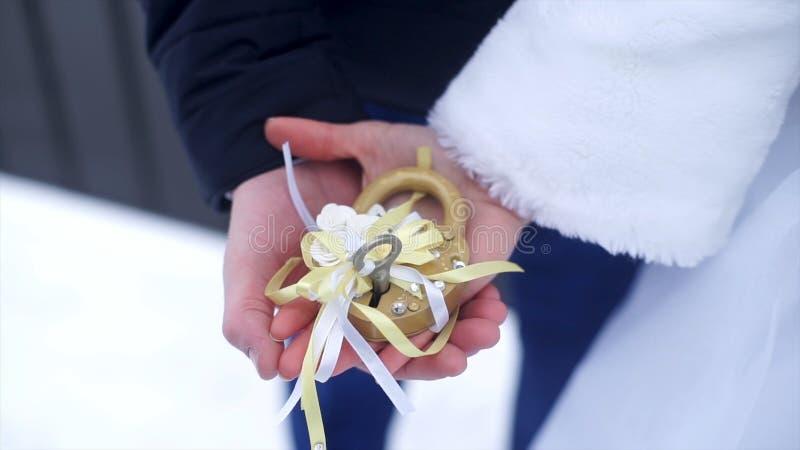 Simbolo di nozze, serratura in mani della sposa e sposo Le persone appena sposate riparano il fissare il ponte come simbolo di am fotografie stock