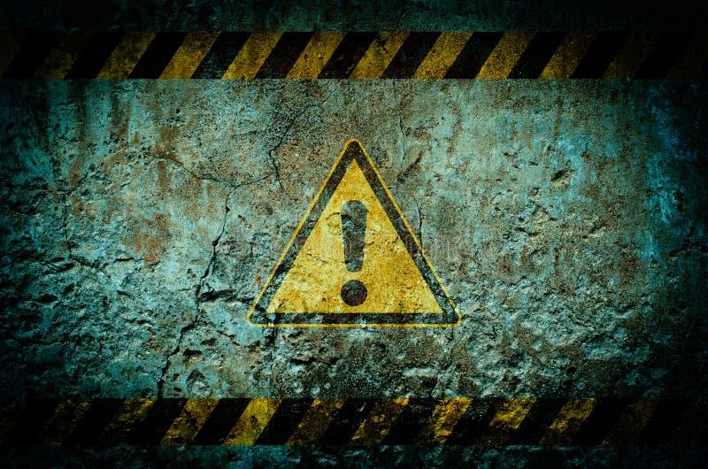 Simbolo di pericolo sul fondo sporco della parete con il lerciume e la scenetta immagine stock