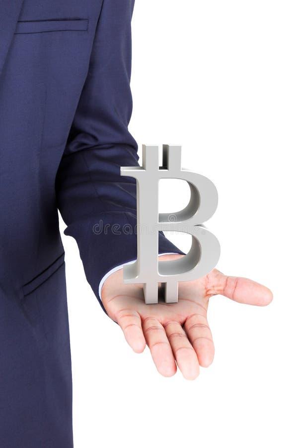 Simbolo di valuta del bitcoin della tenuta dell'uomo di affari fotografia stock