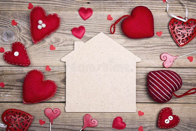 Simbolo domestico con i cuori rossi su fondo di legno con lo spazio della copia fotografia stock