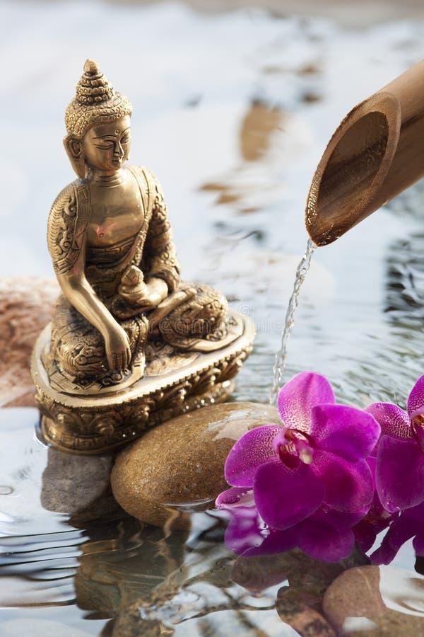 Simbolo religioso con acqua ed i fiori cadenti fotografia stock