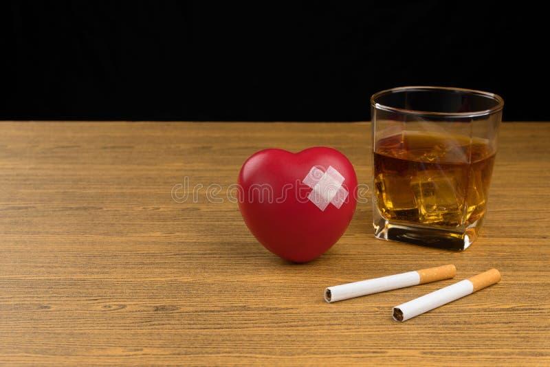 Simbolo rosso del cuore con cerotto adesivo, due sigarette e un vetro del whiskey di bourbon fotografie stock libere da diritti