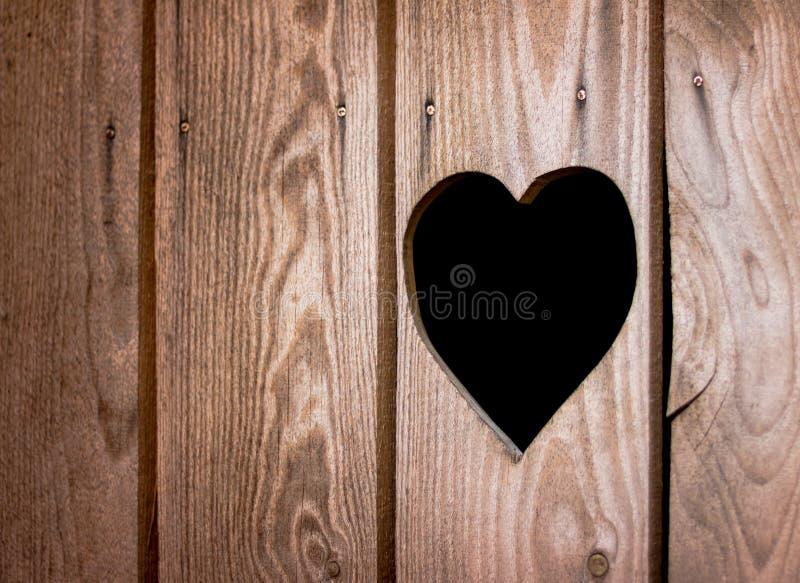 Simbolo scolpito del cuore in porta di legno fotografia stock
