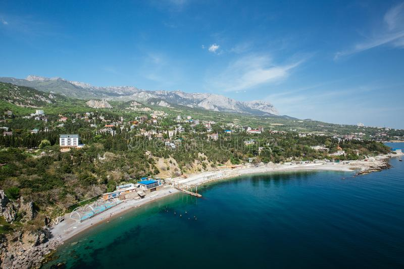 View from a rock at a city beach. Simeiz, View from a rock Diva at city beach. Blue sky, green trees background royalty free stock photos