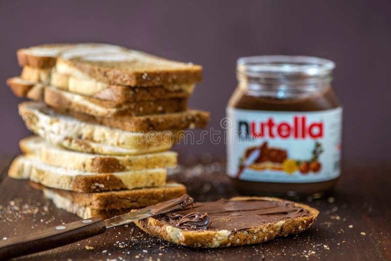 SIMFEROPOL, DE OEKRAÏNE - OKTOBER 3, 2018: Gesneden van marmeren brood en Nutella-hazelnoot spreid kruik op rustieke houten lijst royalty-vrije stock foto's