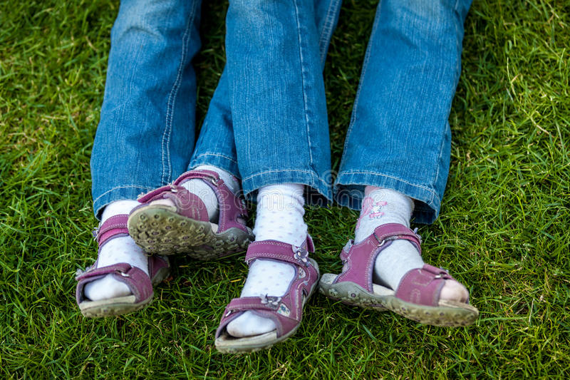 Similar legs in sandals of twin girls royalty free stock image