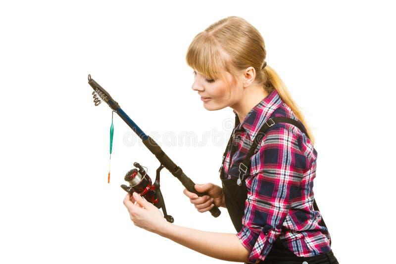 Similing woman wearing check shirt holding fishing rod royalty free stock photo