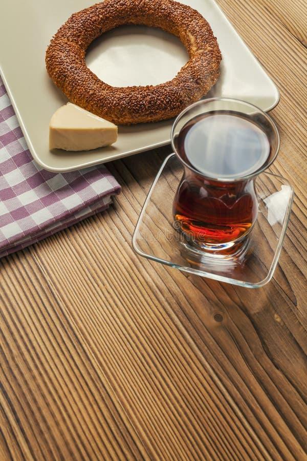 Simit - τουρκικό bagel, τσαγιού και τριγώνων τυρί στον ξύλινο πίνακα στοκ φωτογραφία