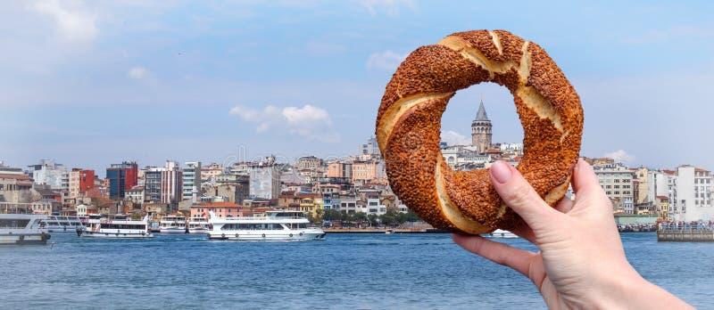 Simit turco tradicional do bagel em uma mão fêmea no fundo do panorama de Istambul e da torre de Galata fotos de stock royalty free
