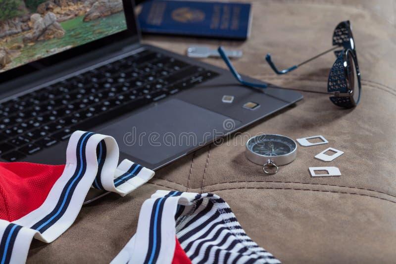 Simkaarten, kompas, zonnebril en zwempak op een open moderne laptop achtergrond Het voorbereidingen treffen voor een strandvakant royalty-vrije stock foto