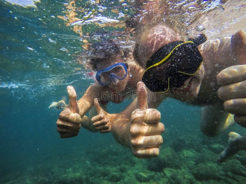 Simma för par som joyfully är undervattens- i havet arkivbilder