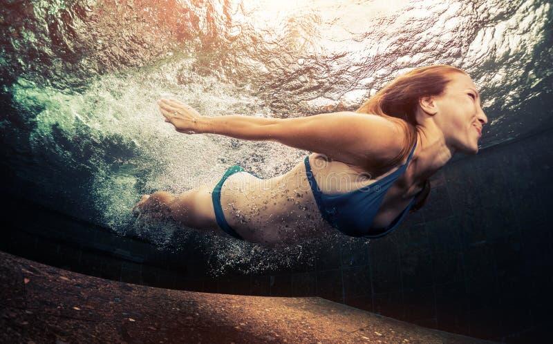 Simma för ung dam som är undervattens- arkivbild