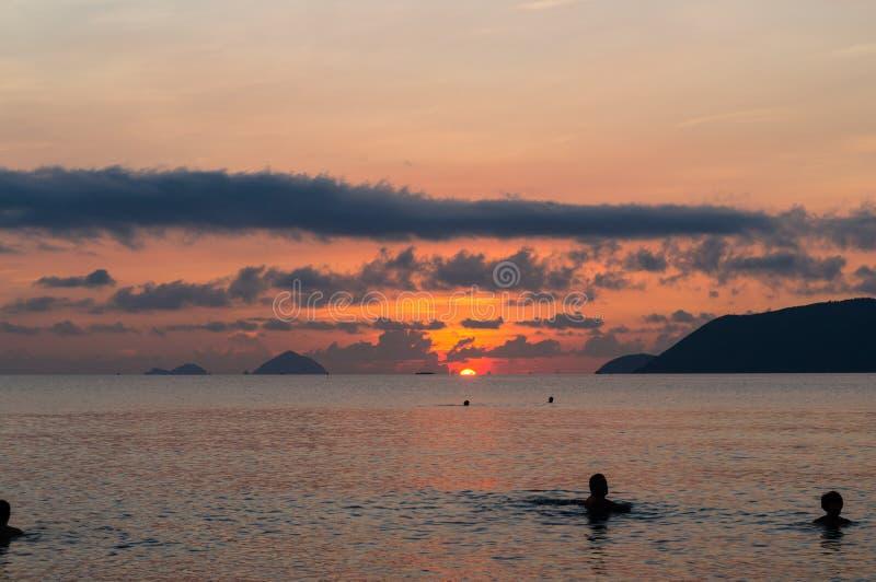 Simma grupp människor i havet på gryning med solen på kanten av horisonten royaltyfri foto